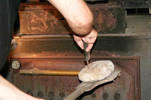 Brot wird in den Holzbackofen geschoben