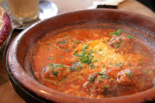 Abbildung ein marokkanischer Kochtopf mit Tomatensoße, Eiern und Hackfleischbällchen in einem Restaurant in Marrakesch