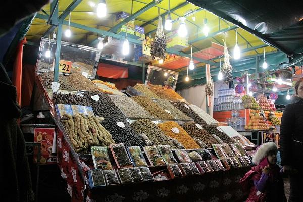 Abbildung zeigt eine Stand mit getrockneten Früchten auf dem Markt in Marrakesch bei Nacht