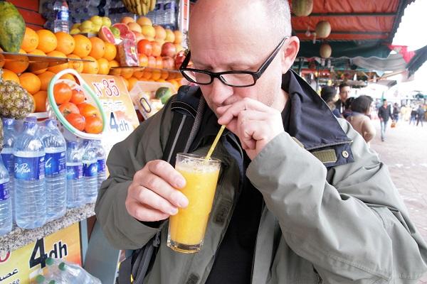 Abbildung ein Franke trinkt frisch gepressten Orangensaft auf dem Djemaa el Fna in Marrakesch
