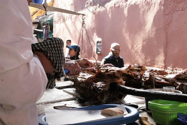 Abbildung gebackenes Schaf auf Holzspieß wird in Marrakesch auf dem Markt angeboten