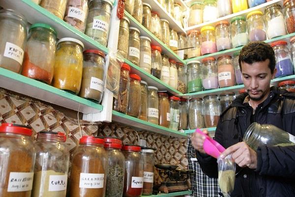 Abbildung Gewürzhändler füllt in seinem Stand auf dem Markt in Marrakesch Gewürze ab
