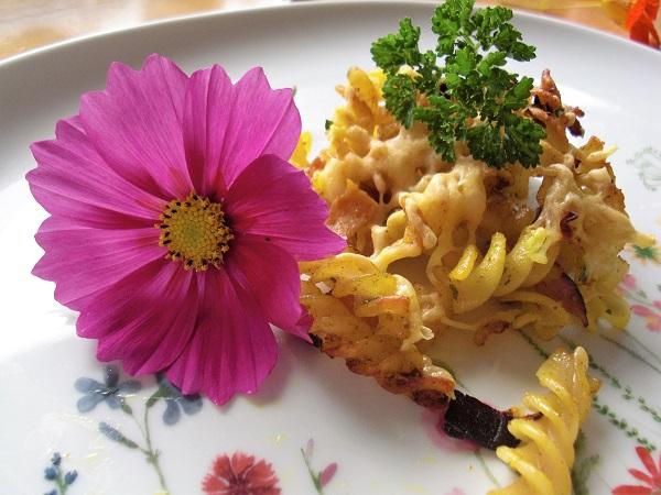 Abbildung gebratene Spiralnudeln mit Kochschinken auf Teller mit Lila Blumenblüte