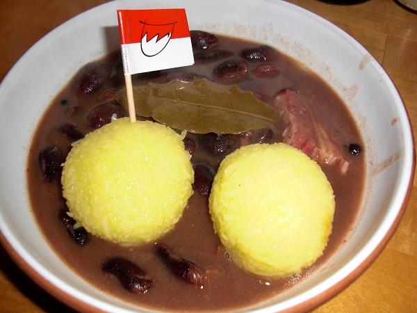 Abbildung zwei Klöße mit fränkischen Feuerbohnenkerne und geräuchertem Bauchfleisch in einem tiefen Suppenteller