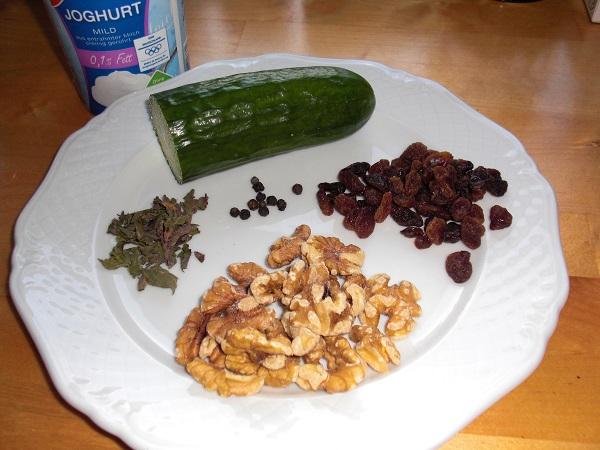 Abbildung Zutaten für persischen joghurtdip Gurke, Rosinen, Walnüsse und Pfefferminzblätter