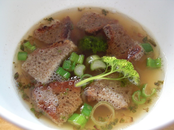 Abbildung Suppe mit Brotscheiben und Kräutern in einem weißen Teller