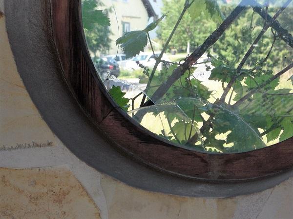 Foto rundes Holzfenster mit zerbrochener Fensterscheibe