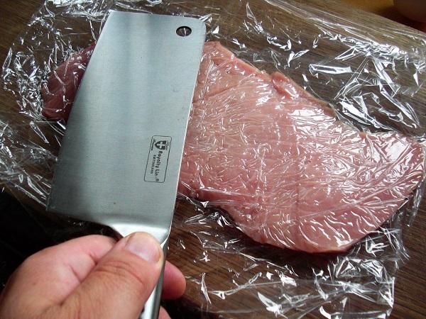 Das Kalbsschnitzel wird in Frischhaltefolie eingewickelt und anschließend mit einem breiten flachen Gegenstand flach gekloppft