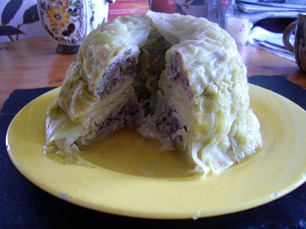 Foto Gugelhupfkuchen aus Weißkohlblätter und Bratwurstbrät angeschnitten auf einem gelben Teller