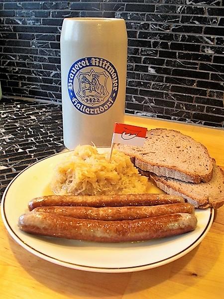 Foto drei Bratwürste mit Sauerkraut und Brotscheiben auf einem weißem Teller mit Goldrand