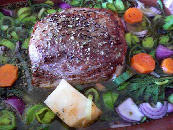 Schweinebraten mit Gemüse in einem Schmortopf geben