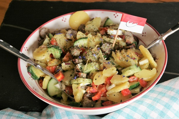 Foto Kartoffelsalat mit Bratwurstscheiben in einer hellen Keramikschüssel