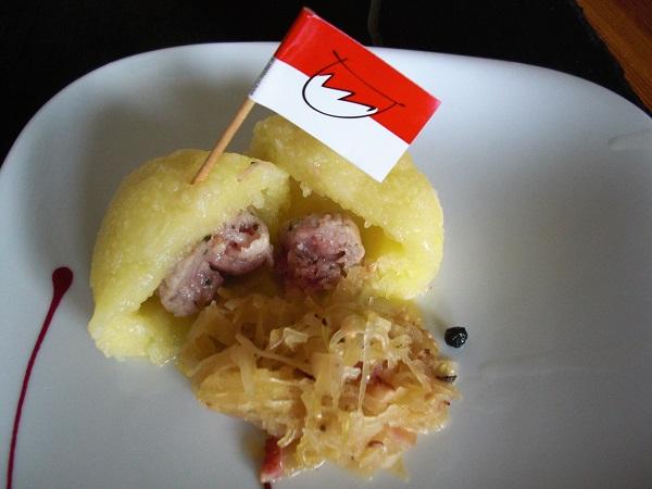 Foto Kloß halbiert mit Bratwurstbrätfüllung auf einem weißem Teller mit Sauerkraut