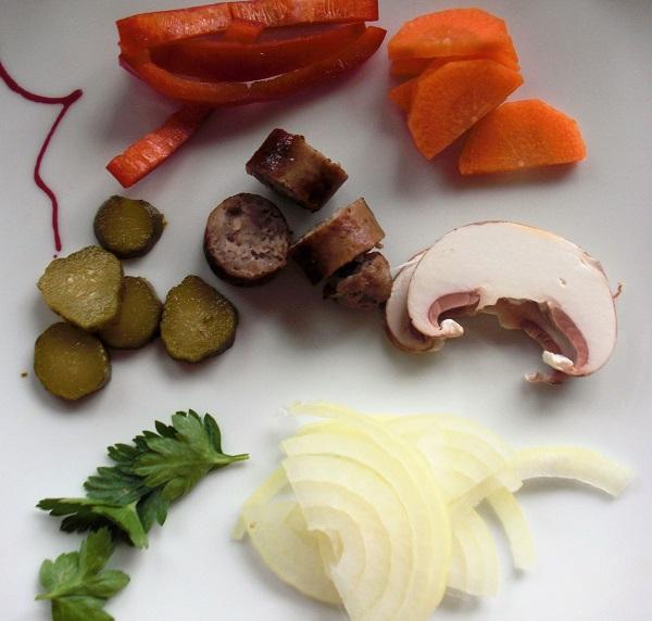 Foto kleingeschnittene Bratwurst Essiggkurke Zwiebeln Karotten auf weißem Teller