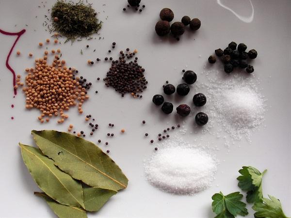 Foto Gewürze Lorbeerblatt Senfkörner Wacholderbeeren Salz Zucker Pfeffer Dill Petersilie auf weißem Teller