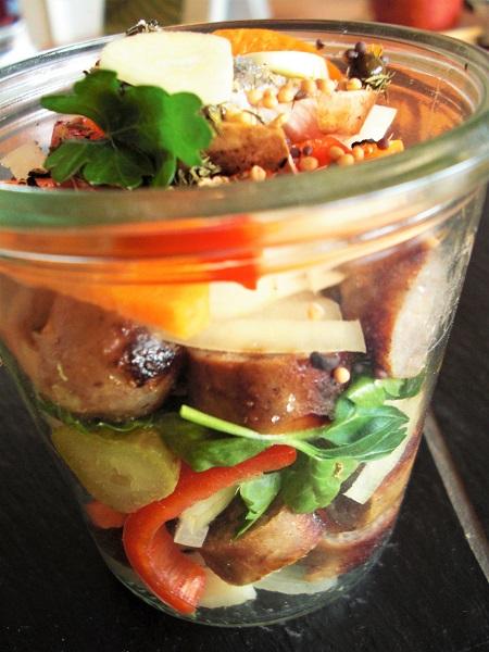 Foto gebratene Bratwurstscheiben mit Zwiebeln, Essiggurken und Paprika im Einweckglas