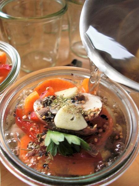 Foto Einweckgläser mit Gemüse und Wurst werden mit Essigsud aufgefüllt