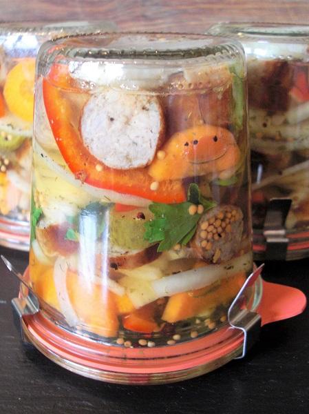 Foto Einweckglas mit Gemüse und Bratwurstscheiben auf dem Kopf gestellt