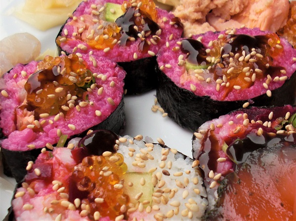 Foto kleine Sushischeiben mit rot gefärbten Reis und mit Fischeier und Sesam bestreut