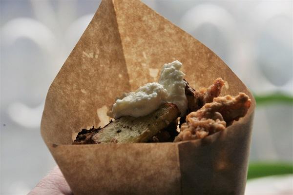 Foto frittierte Karpfenstücke mit Rosmarinkartoffeln und Meerrettichdip in einer braunen Papiertüte