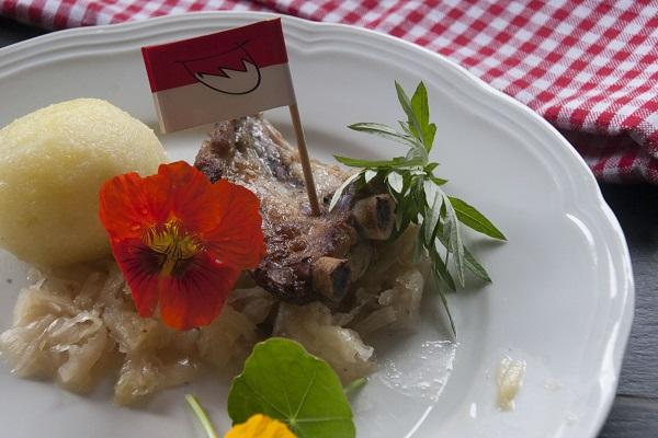 Foto Rifferla Schweinerippchen auf Sauerkraut mit einem fränkischen Kloß auf einem weißen Porzellanteller angerichtet