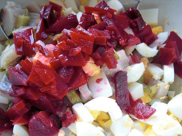 Nahaufnahme Matjessalat mit gekochtem Ei roter Bete Äpfeln Matjesfilets Johgurt und Essiggurken