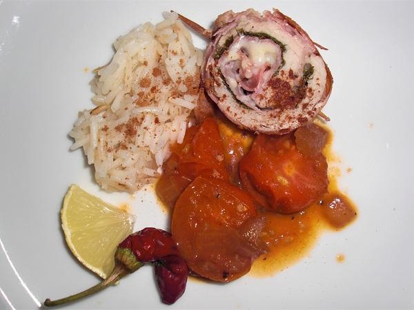 Foto Schweinefleisch gerollt mit Schinken-Käse-Füllung und mit Kirschtomaten und Reis auf weißem Teller angerichtet
