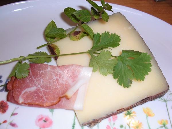 Foto Manchego-Käse mit rohem Schinken und Pefferminz- und Korianderzweig auf einem Teller mit Blumenmuster