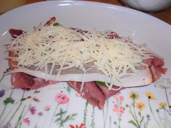 Foto Schweineroulade mit rohem Schinken und gehobeltem Manchego-Käse belegt