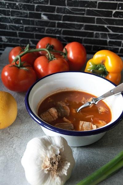 Foto weiß emailierte Schüssel mit blauem Rand und einer roten Fischsuppe daneben eine Knoblauchknolle Zitrone Tomate gelbe Paprika und einer Frühlingszwiebel