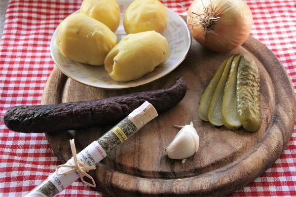 Foto Zutaten für fränkische Bauernpfanne. Zwiebeln, Kartoffeln, Knoblauch, Essiggurken und geräucherte Bratwürste