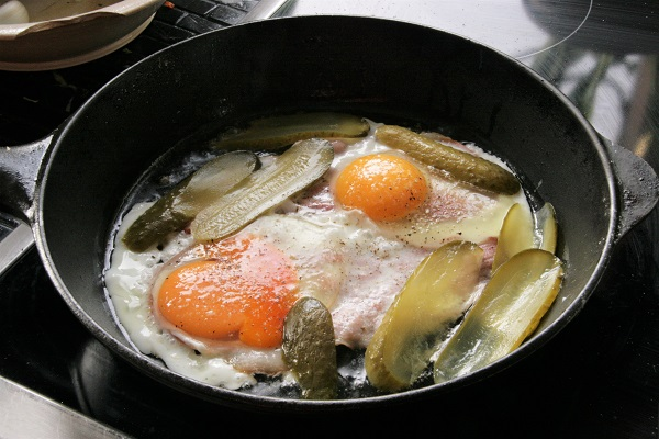 Foto Speck, Eier und Essiggurken werden in einer Pfanne angebraten