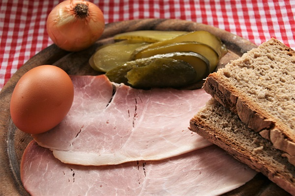 Foto Zutaten für fränkisches Bauernfrühstück Schinken, Essiggurken, Ei und Brot auf Holzteller