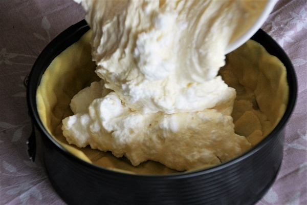 Quarkmasse wird in eine Kuchenform gegossen