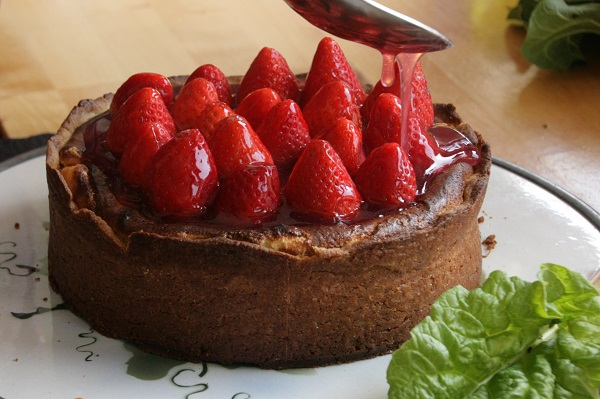 Käsekuchen mit Erdbeeren wird mit Tortenguss begossen